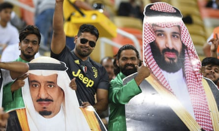 Saudi football fans hold pictures of Prince Mohammed (R) and King Salman