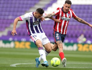 oscar plano of real valladolid scores their side's first goal whilst under pressure from jose gimenez of atletico madrid.