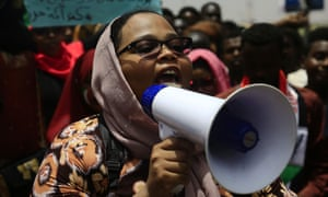 A Sudanese woman speaks through a loudspeaker at protests in Khartoum.