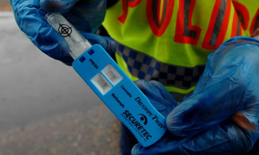 A police officer holds a drug tester. Under the government's proposed trial, saliva, hair follicle and urine testing would be used to detect drugs including ecstasy, marijuana and ice.