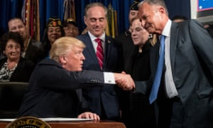 Orange Donald Trump shakes hands with Isaac Perlmutter (right).