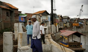 Residents walk on a concrete floodwall by Ciliwung river in Jakarta