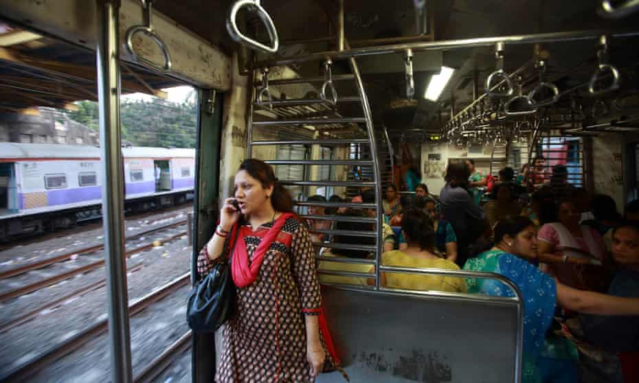 A passenger speaks on the phone near the open doorway of a women-only train in Mumbai.