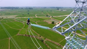 A maintenance worker checks power lines in Laian, China