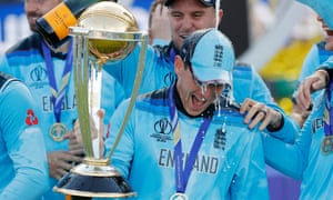 Eoin Morgan keeps hold of the World Cup trophy while his England teammates break out the champagne at Lord's
