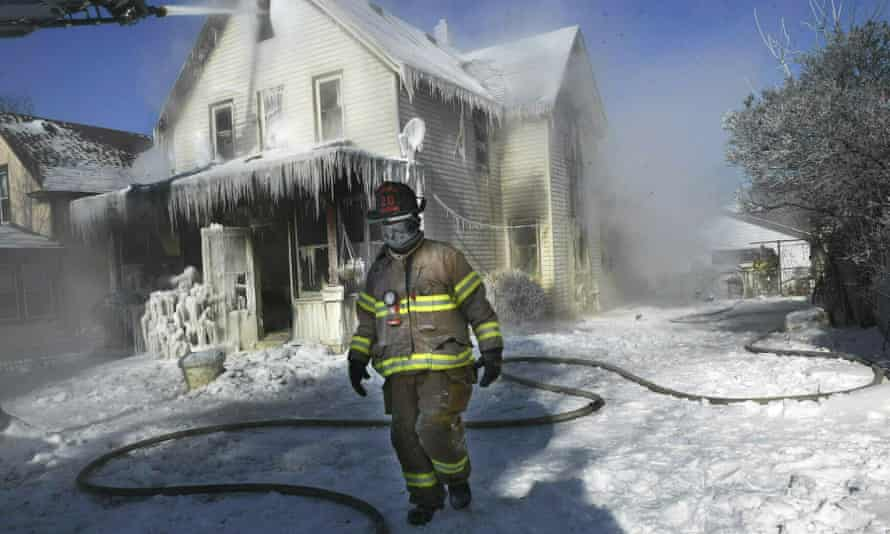 A firefighter, his clothing frozen from the extreme cold, walks by an early morning house fire in St. Paul, Minnesota.