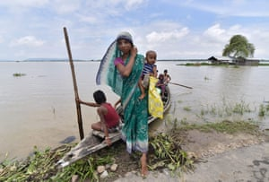 A woman and her child step off a boat in the flood-hit village of Balimukh Ashigarh in Morigaon, India