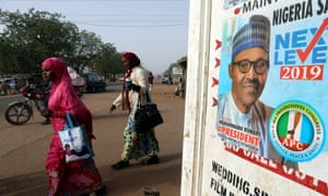 Women walk past campaign posters for President Buhari.