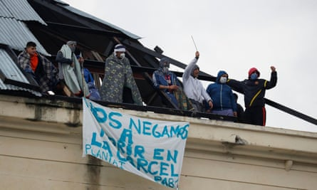 Inmates are seen on the roof of the Devoto prison in Buenos Aires, Argentina, with a banner that reads 'We refuse to die in jail' during a riot demanding health measures against coronavirus on 24 April.