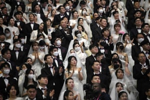 Brides and grooms clapping in audience wearing face masks