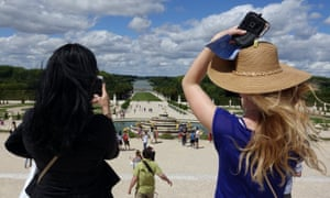 Tourists take pictures of the gardens at Versailles.