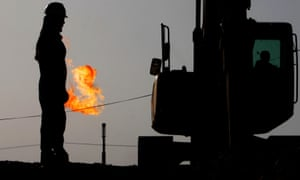 A gas flame burns behind oilfield workers in Bahrain.
