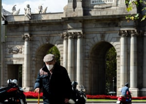 A man wearing a face mask in front of the Puerta de Alcalá, Madrid.