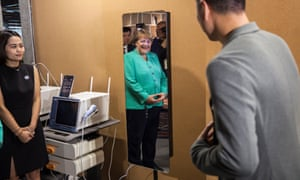 German Chancellor Angela Merkel looks at her reflection in a machine mirror while visiting the iCarbonX factory in Shenzhen, Guangdong Province, China, 25 May 2018.