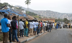 People queue to cast their vote at a polling station during Sierra Leone's presidential election