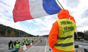 A man wearing a gilet jaune with a 'Macron resign' slogan protests against rising oil prices and living costs near Marseille.