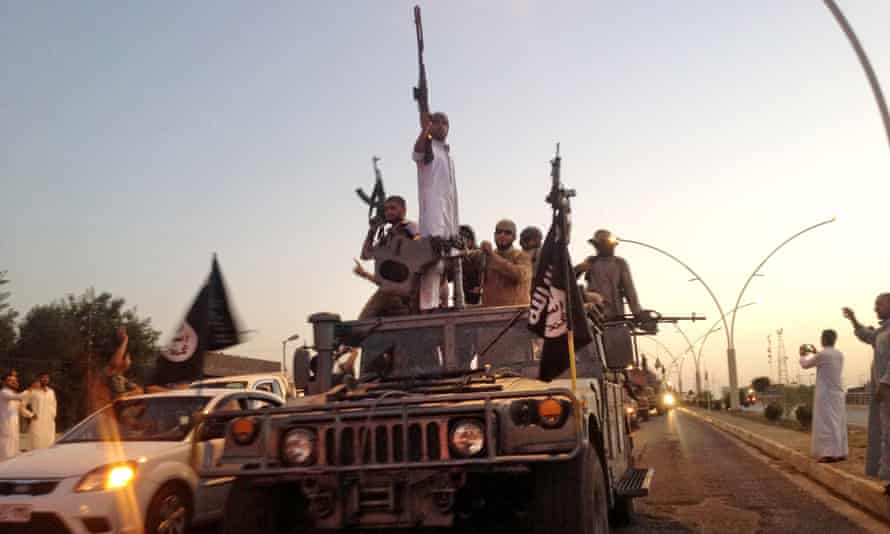 Islamic State fighters parade in a commandeered Iraqi security forces armored vehicle