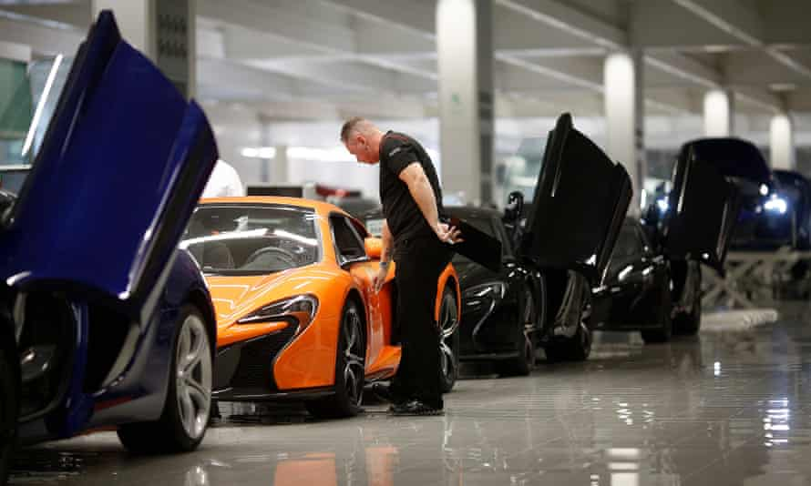An employee inspects a McLaren 650S at the carmaker's headquarters in Woking, Surrey