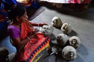Manju Saha, an idol maker, prepares faces of the goddess Durga