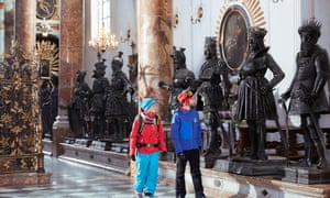 Two tourists in Innsbruck's Hofkirche, with statues surrounding the tomb of Emperor Maximillian