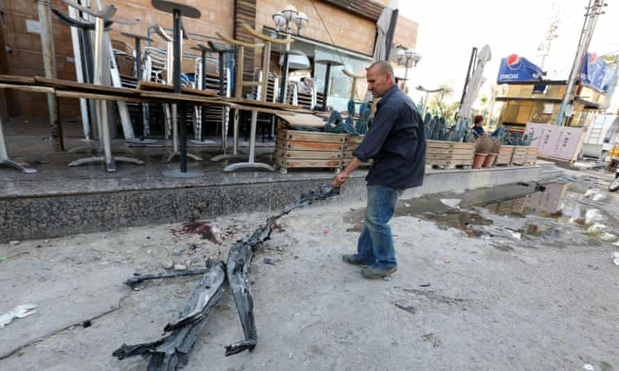 A man drags a piece of debris from the site of the bombing in Baghdad.