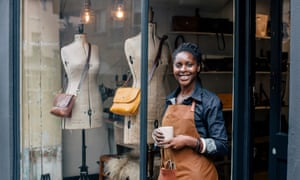 A small business owner looks to camera outside her handbag shop.