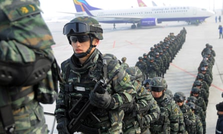 Paramilitary policemen board a plane in Urumqi as they head for an anti-terrorism oath-taking rally in Kashgar.