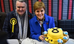 Nicola Sturgeon with the Ochil & South Perthshire SNP candidate John Nicolson posing with an SNP-decorated cake at a Syrian bakery in Alloa, Scotland.
