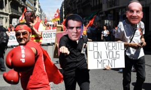 People wearing masks protest against the policies of Valls.