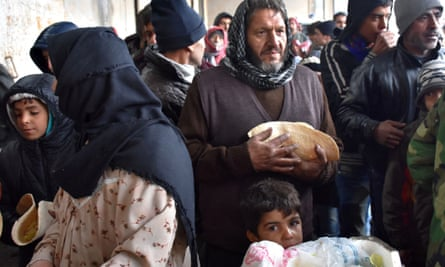 Syrians receive food at warehouse outside Aleppo