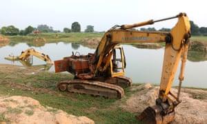 Burnt and damaged sand excavators lying on the river near Jatpura village