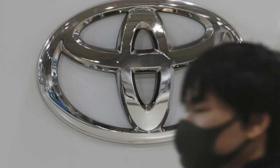 A man wearing a face mask walks by the logo of Toyota Motor Corp. at its showroom in Tokyo.