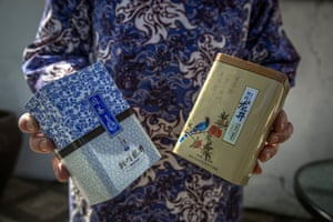 After the process of making Longjing tea, Wang Yuebao shows the tea boxes that she sells