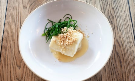 A square piece of brill in a butter sauce, in the centre of a large round white plate, shreds of dark green monk's beard to the side