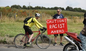 A protester offers advice to a cyclist on the road to Turnberry with a sign saying: 'Caution! Racist ahead'