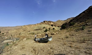 Yemeni men inspect an abandoned boat at a drought-affected dam on the outskirts of Sana'a.
