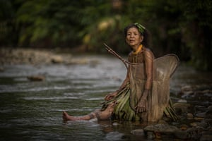 Two women of the tribe wear traditional handmade skirts to catch fish in the local river