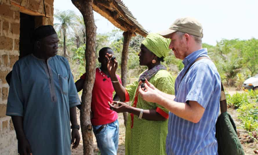 WasteAidUK project manager Mike Webster and Women's Initiative – The Gambia leader Isatou Ceesay demonstrate organic fuel briquettes to a community.