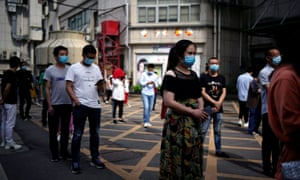 Residents wearing face masks line up for nucleic acid testings at a residential compound in Wuhan, China 15 May 2020.