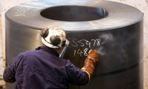 A worker chalks up a number on a roll of sheet metal