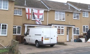 A white van parked in front of a house hung with the St George's flag