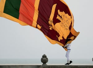 A Sri Lankan officer lowers the national flag at a square in Colombo, Sri Lanka, on March 23.
