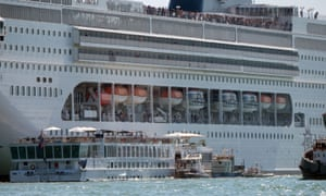 The cruise ship next to the smaller tourist boat in Venice