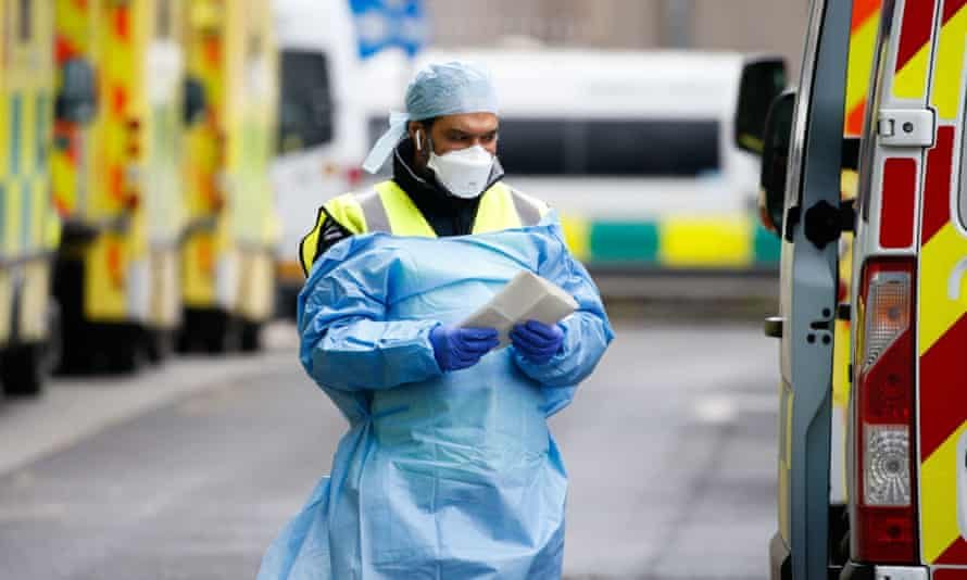 A medical worker wearing a face mask and protective clothing walks beside ambulances outside the emergency department of the Royal London Hospital