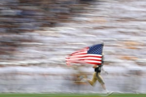 Annapolis, USTravis Brannan #22 of the Navy Midshipmen carries the U.S. flag as he and teammates take the field before playing against the East Carolina Pirates during the first half at Navy-Marine Corps Memorial Stadium