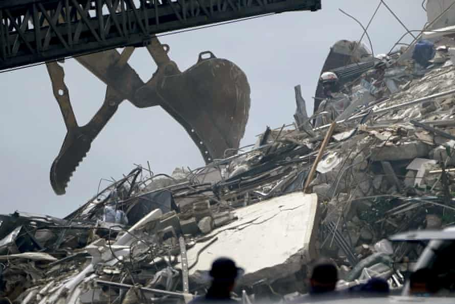 Search and rescue workers go through rubble hoping to detect any sounds coming from survivors.