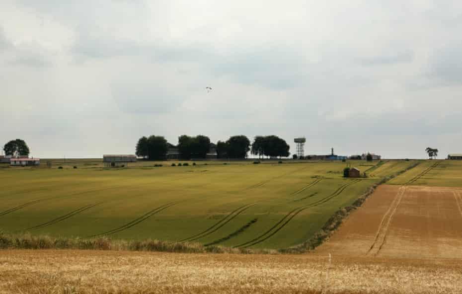 Fields surrounding Netheravon airfield in Wiltshire, with a parachutist descending