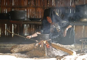 A woman in a remote Akha village in the hills of northern Laos making a meal over a fire outside her hut.