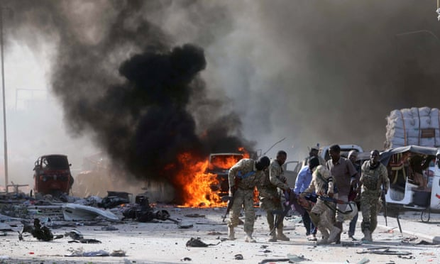 Solider evacuating one of the wounded people in the bombing in Mogadishu