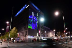 A large projection of Leicester striker Jamie Vardy is seen on the side of a building.